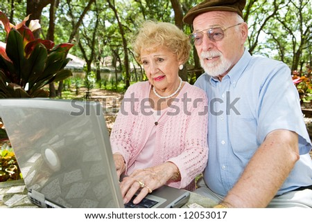 Senior couple with laptop browses the internet in a beautiful outdoor setting. - stock photo