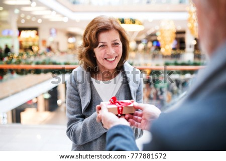 Senior couple with present doing Christmas shopping.