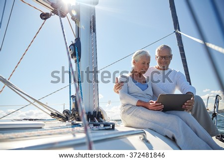 senior couple with tablet pc on sail boat or yacht - stock photo