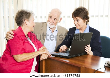 Senior couple with their financial adviser, going over their retirement income on her computer. - stock photo