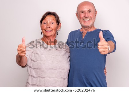senior couple with thumbs up smiling