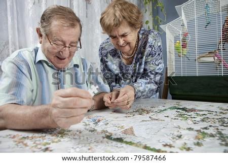 Senior couple working on a puzzle - stock photo