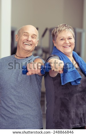 Senior couple working out together with dumbbells giving the camera happy friendly smiles in a healthy active lifestyle concept - stock photo
