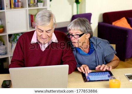 Senior couple writing emails on their notebook computer and tablet. - stock photo