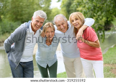 Senior couples having a good time in countryside - stock photo