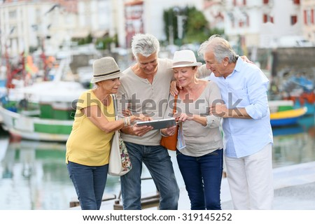 Senior couples looking at map on traveling journey - stock photo