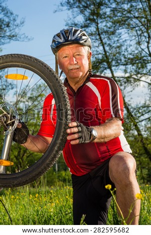 Senior cyclist checking his bike - stock photo