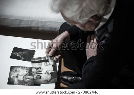 Senior depressed man looking at old photos - stock photo