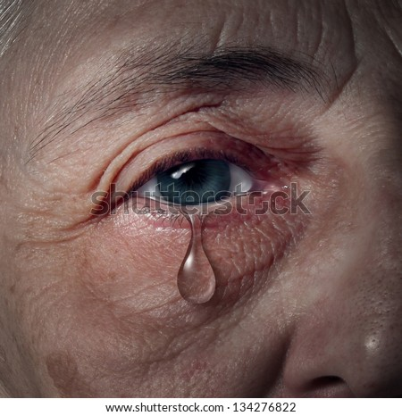 Senior depression and elderly mental health issues related to loneliness and emotional illness based on grief or chemical imbalance as anxiety in a close up of an aging human eye crying a tear drop. - stock photo