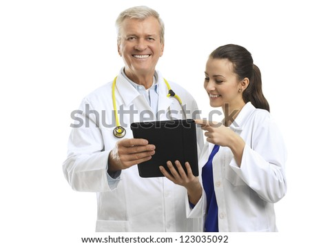 Senior doctor and her assistant watching his digital tablet, and discussing reports. Isolated on white background. - stock photo