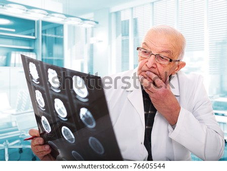 senior doctor at work in his office