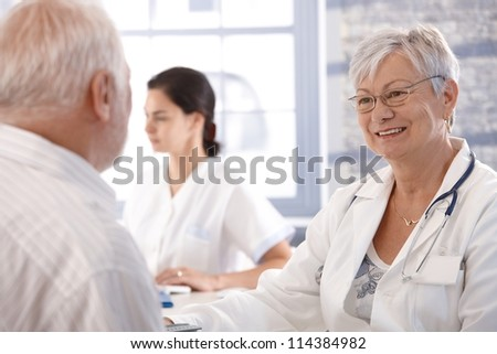 Senior doctor consulting with old man at her office. - stock photo