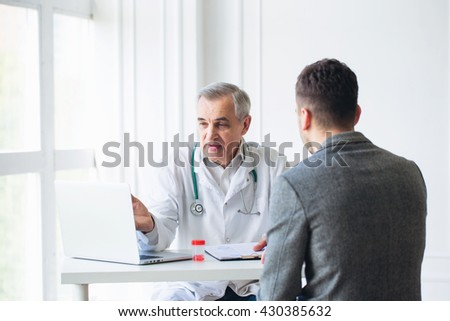 Senior doctor consults young patient - stock photo