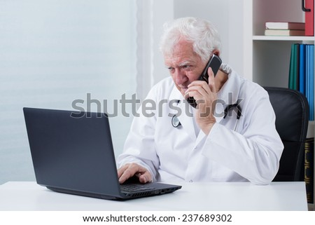 Senior doctor in his office and telephone consultation
