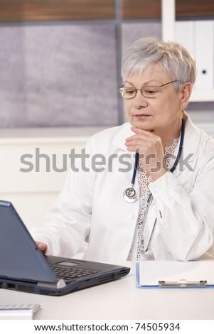 Senior doctor looking at computer screen, thinking.? - stock photo