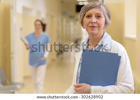 Senior doctor standing in hospital hallway holdings patient files - stock photo