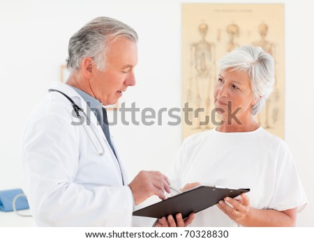 Senior doctor talking with his sick patient - stock photo