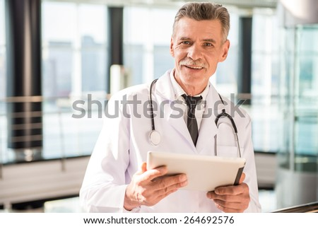 Senior doctor using his tablet in hospital. - stock photo