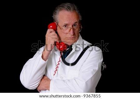 Senior doctor wearing a stethoscope isolated on black and talking on a telephone
