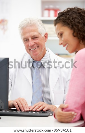 Senior doctor with female patient - stock photo