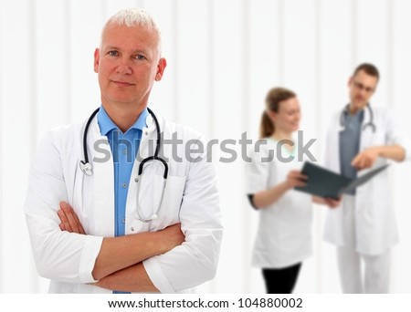 Senior doctor with his arms crossed and a stethoscope around his neck standing in front of his colleagues