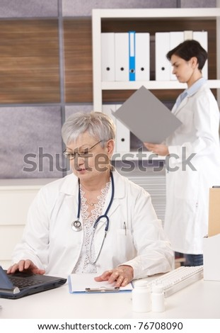 Senior doctor with young specialist working together in office, using computer and folder.?