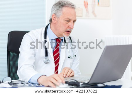 Senior doctor working at his laptop - stock photo