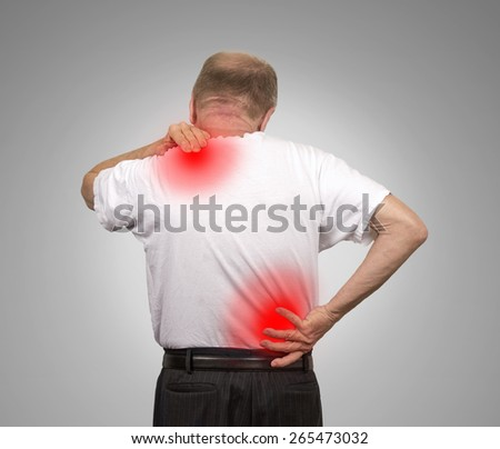 Senior elderly man with lower and upper back pain isolated on gray wall background. Spinal cord problems - stock photo
