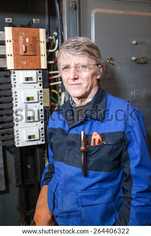 Senior electrician in blue uniform standing near high voltage panel