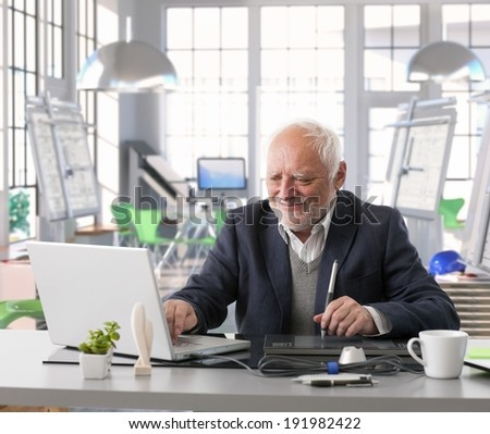 Senior engineer sitting at desk doing design work with computer at architect studio. - stock photo