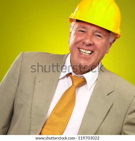 Senior Engineer Standing And Smiling On Yellow Background - stock photo