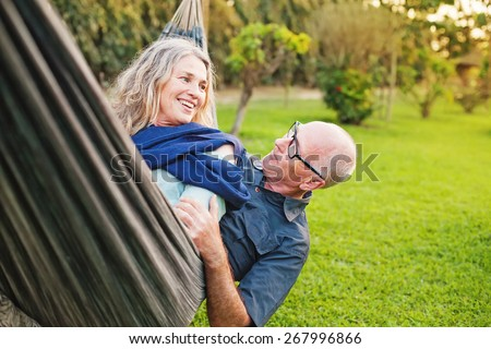 Senior european couple talking lying down and playing in a hammock - stock photo
