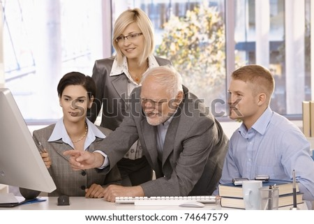 Senior executive discussing computer work with businessteam, pointing at screen, smiling.? - stock photo