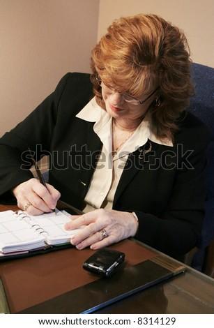 Senior executive woman writing in agenda - stock photo