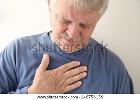 senior experiencing discomfort in his chest - stock photo