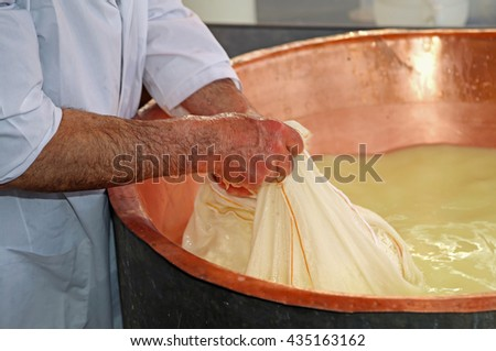 Senior expert cheesemaker collects the cheese with the tarp from the large copper cauldron filled with milk and whey