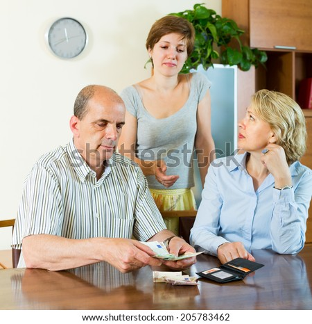Senior family couple with adult daughter discussing budget  - stock photo