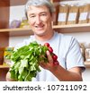 Senior farmer selling his vegetables in his farm shop - stock photo