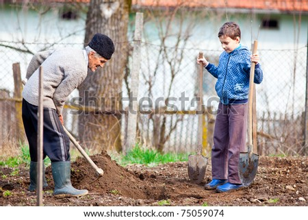 Senior farmer teaching his grandson how to plant trees in the garden - stock photo