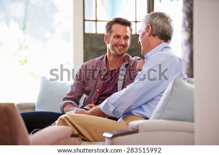 Senior Father With Adult Son Relaxing On Sofa At Home - stock photo