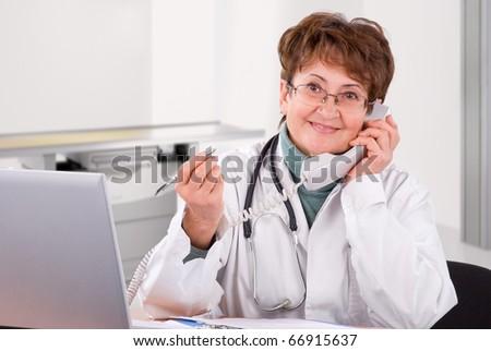 Senior female doctor calling on phone, smiling. - stock photo