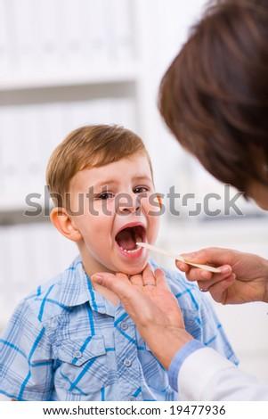 Senior female doctor examining little child boy. - stock photo