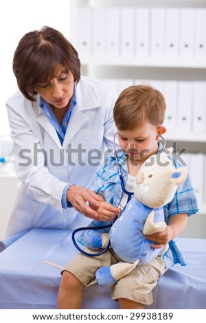 Senior female doctor examining little child boy.