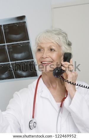 Senior female doctor examining x-ray while talking on landline - stock photo