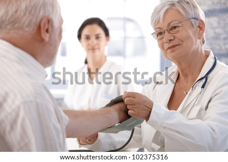 Senior female doctor measuring old man's blood pressure. - stock photo