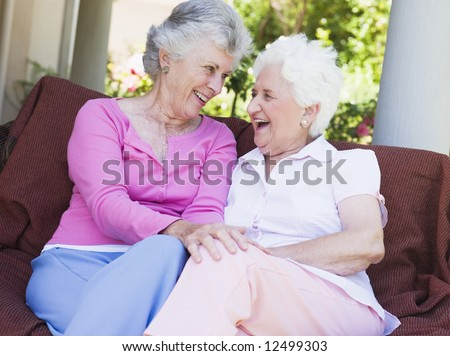 Senior female friends chatting together sitting on garden seat - stock photo