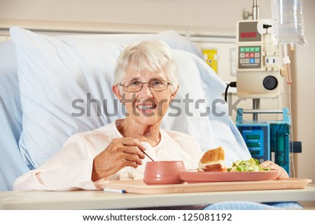 Senior Female Patient Eating Meal In Hospital Bed - stock photo