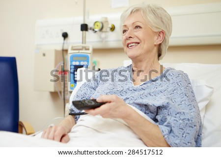 Senior Female Patient Watching TV In Hospital Bed - stock photo