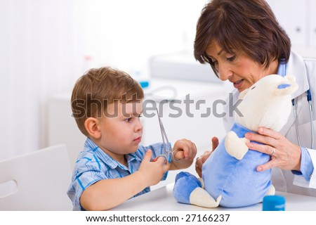 Senior female  pediatrician playing with child at doctors office.