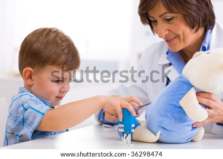 Senior female  pediatrician playing with child at doctors office. - stock photo